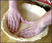 Patting the dough into the pie pan